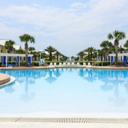 Cabana West Apartments exterior: large pool with well kept landscape (palm trees and a fountain)
