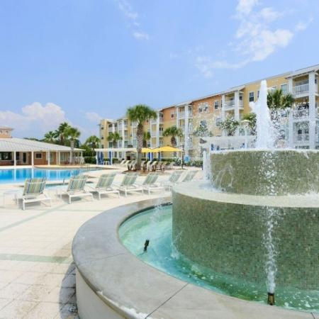Cabana West Apartments exterior: backside view of fountain and large pool with beach chairs