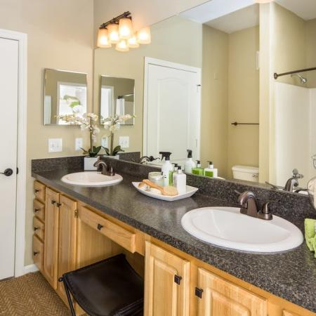 Grandeville at River Place Interior | Bathroom | Two sinks | Large mirror | Bath tub | Shower | Toilet