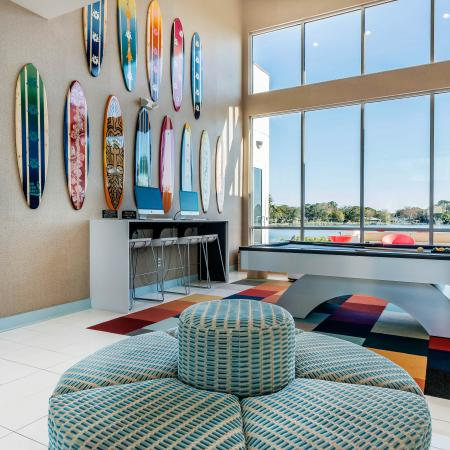 Long glass windows next to a wall with decorative surf boards hanging up. Pool table in the center of the room on top of a checkered colored rug and next to a circular chair.