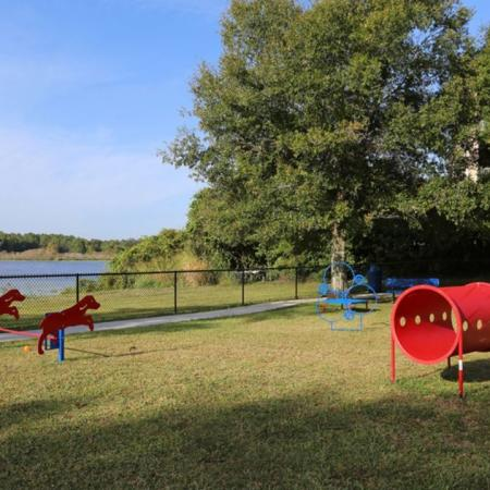 Harbortown Luxury Apartments, exterior, dog park, red and and blue agility toys, fenced in, view of water, trees, grass