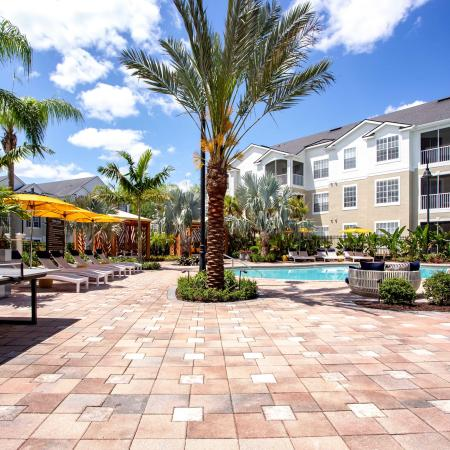 Grandeville at River Place Exterior | Outdoor pool | Palm trees | pool chairs | Ping pong table