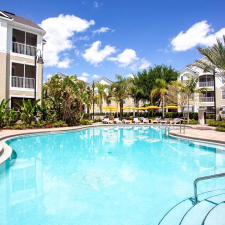 Grandeville at River Place Exterior | Outdoor pool | Palm trees | Pool chairs | Residential building