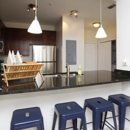 Cabana West Apartments interior: kitchen area with bar-style counter, sink, fridge, and more