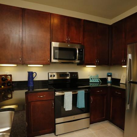 Cabana West Apartments interior: kitchen area with microwave, oven, fridge, and cabinets