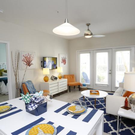 Cabana West Apartments interior: living area with dining table, opening to the bedroom, and door that goes outside