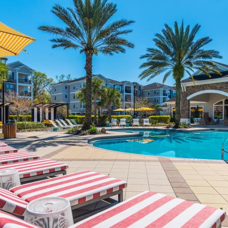 Citigate Apartments Exterior | Resort style pool | Palm trees | Pool chairs | Canopies