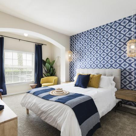 Harbortown Luxury Apartments, interior, blue and white wall paper accent wall, blue and white bed, carpet, large window, blue drapes, dresser