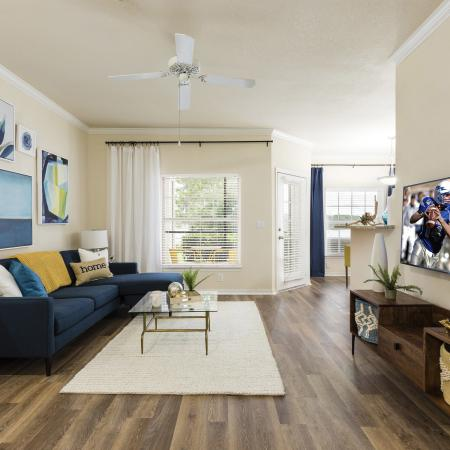 Harbortown Luxury Apartments, interior, living room, wood floor, blue couch, white area rug, tv, large windows, bright, ceiling fan, blue wall art