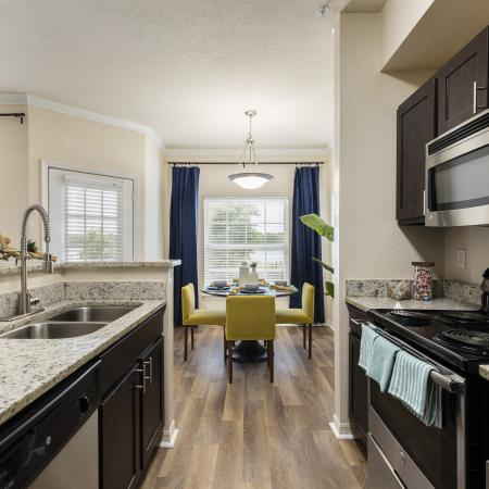 Harbortown Luxury Apartments, interior, kitchen, dining room, dark cabinets, stainless steel appliances, dishwasher, stove/oven, microwave, yellow chairs, dining table, large windows, blue drapes