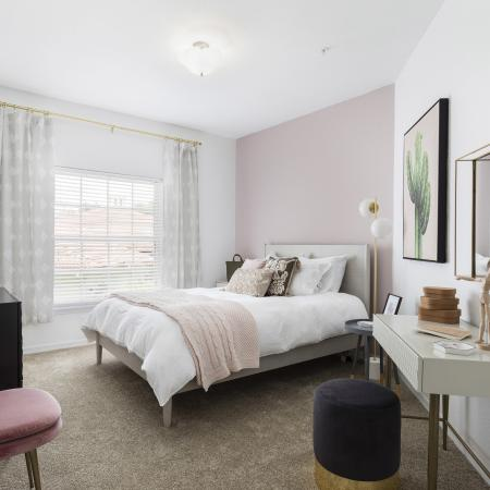 Harbortown Luxury Apartments, interior, bedroom, pink, white tan, decor, bed, pink chair, vanity with mirror, large window