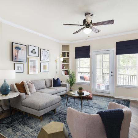 Harbortown Luxury Apartments, interior, living room, gray sectional, large windows, blue area rug, pink chair, wall art, ceiling fan