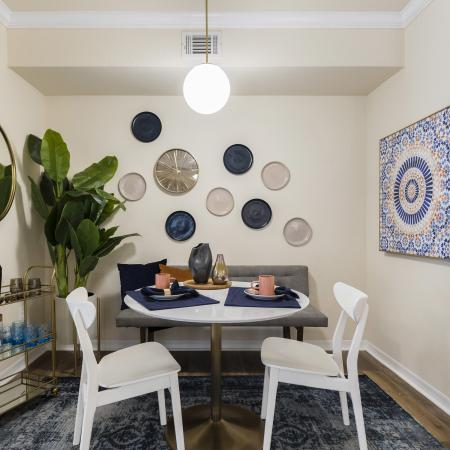 Harbortown Luxury Apartments, interior, dining room, white table, two chairs, gray bench, plant, wall art