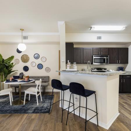 Harbortown Luxury Apartments, interior, dining room, kitchen, breakfast bar seating for two, dark cabinets, stainless steel appliances, microwave, stove/oven, blue area rug