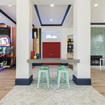 Harbortown Luxury Apartments, interior, spacious game room, large windows, billiard table, chair, green tile fire place, books, blue doorways, arcade games, red doors