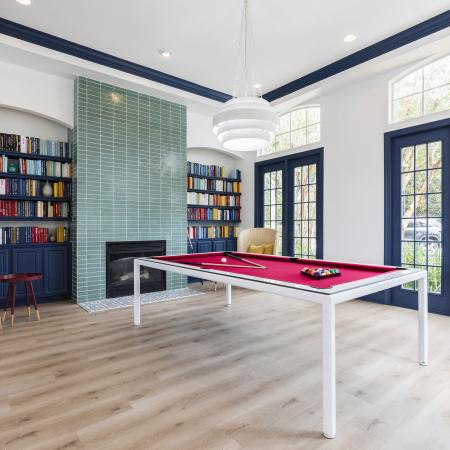 Harbortown Luxury Apartments, interior, spacious game room, large windows, billiard table, chair, green tile fire place, books, blue doorways