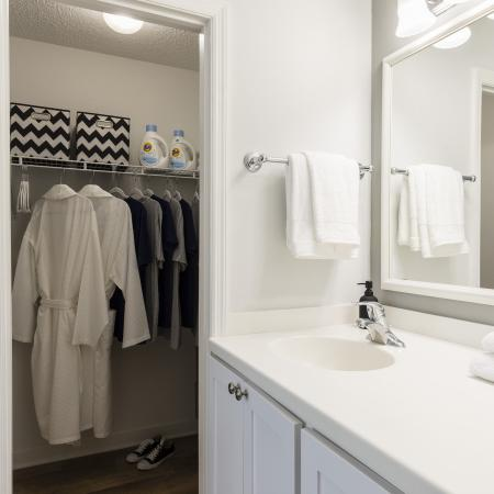 White bathroom that has a door leading into a walk in closet. Sink with a white counter top and white towels