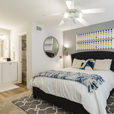 Bedroom with a large bed with a white comforter on it and a blue knitted throw blanket. White ceiling fan. Light brown carpet, grey accent wall with artwork on it above the bed. Mirror in a circle shape on the wall next to the bed. There is