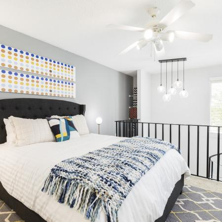 Large bed next to a railing that leads down a spiral stair case that goes into the living room. Light grey wall against the bed that leads into a nook storage area. White ceiling fan above the bed.