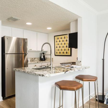Another view of the kitchen with a large stainless steel fridge. Two in the ceiling round lights on a popcorn ceiling. Two bar stools against the counter top with a silver sink in the granite counter top.