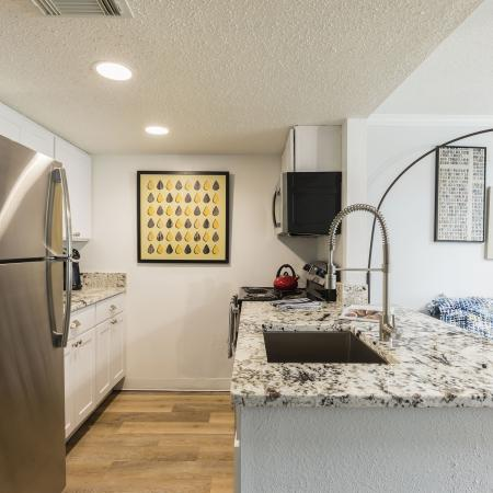 Kitchen area with granite counter tops. Singular sink with stainless steel fridge across from it and white cabinetry.
