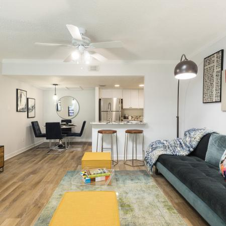 Living room with light hardwood floors. White ceiling fan, dark green/blue plush couch with a few colorful throw pillows. Two yellow coffee tables in front of a TV mounted on the wall that is above a table. The back left of the room has a c