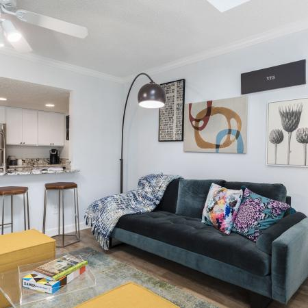 Dark green\blue plush couch with two colorful throw pillows and a blue blanket on the couch.  Four pictures on the wall above the couch. Large overhanging lamp over the couch next to two bar stools under a breakfast bar leading into the kit