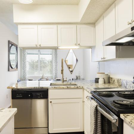Kitchen area with a black gas stove top. Granite counter tops. Silver dishwasher and white counter tops