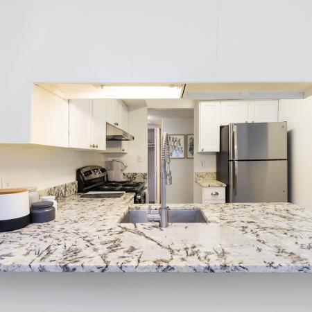 Different view of kitchen area. Back left of the photo there is a stainless steel fridge. Spotted granite counter tops with a singular silver sink. White overhanging cabinetry