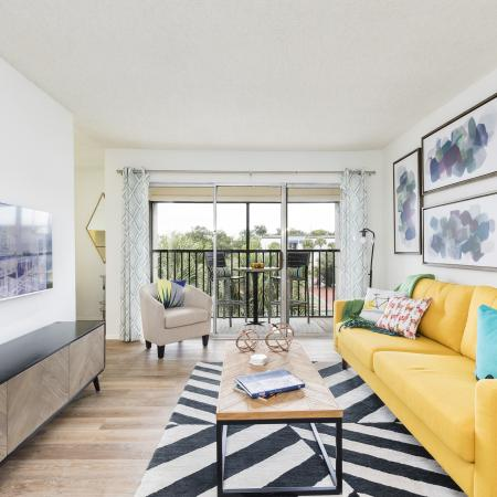 Yellow leather couch with a few colorful throw pillows on it. Coffee table in front of the couch is on top of a black and white rug. Long table against the wall holding a decorative vase with a flat TV on the wall above the table. There is