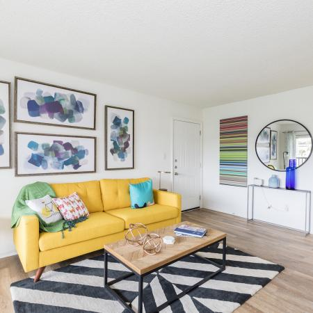 Yellow leather couch on top of a black and white chevron rug. Both adjacent walls have artwork on it and the wall across from the couch has a circle mirror and a small table holding decorative vases. Small coffee table in front of the couch