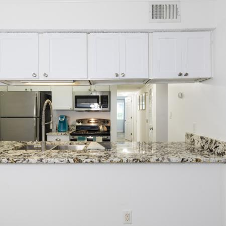 View into the kitchen with white counter tops and silver appliances with a speckled counter top