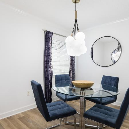 Dining room area with a window in the back corner with blinds and drapes over the window. A circle mirror adjacent to the window. Glass circle table with four plush blue chairs with a chandelier hanging above the table.