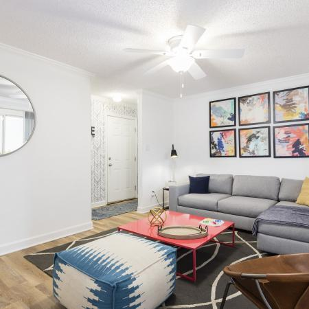 Another view of the living room with the grey couch on the right side and a large circle mirror on the left side of the room on a white wall.