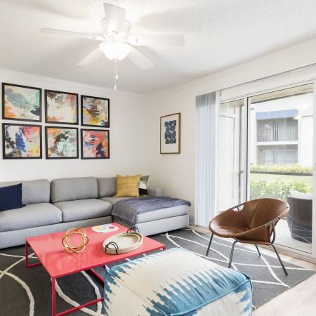 Living room with a grey couch in the back. Decorative wall art above the couch. Red coffee table in the middle of the room with a white ceiling fan. Large grey and white rug on top of the light hardwood floor. Sliding glass door leading out