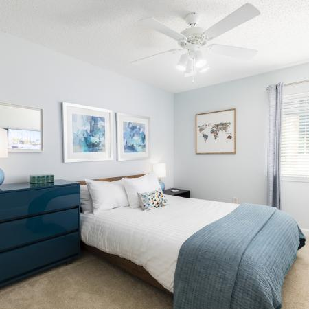 Bedroom with light brown carpet, and light blue walls. Bed with white comforter in the middle of the room next to a window and a turquoise dresser with a lamp on it. There are pictures on the walls with art work on them and a mirror above t
