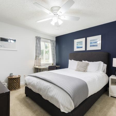 Bedroom area with a large bed with a white comforter on top of it. The bed is against a dark blue accent wall. There is a small window against the corner and a dresser on the other side of the bed. Light brown carpeting.