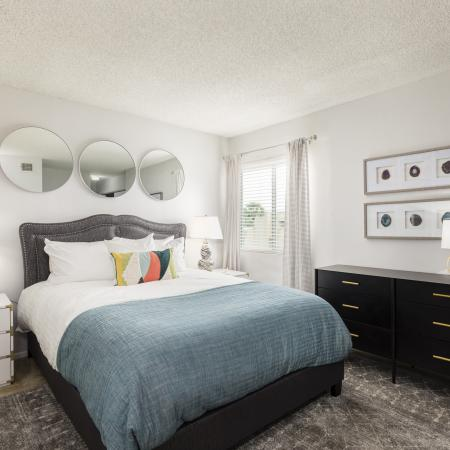 Lakeside villas | Black and white bedroom set | window on the far right end | 3 round mirrors above bed set.
