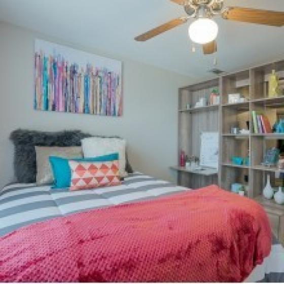 Rio West bedroom with ceiling fan and open wooden shelving