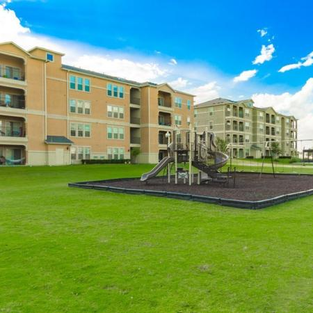 Residents playing at the Children's Playground | Apartment Homes In San Antonio | The Estates at Briggs Ranch