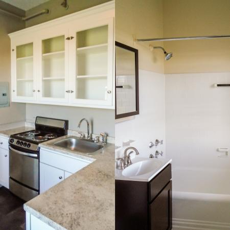 Glass-fronted kitchen cabinets in kitchen / bath with large mirror, full-size tub/shower combo at apartments in Brookline, MA.