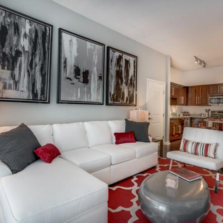 Image of The Marq Highland Park's apartment interior furnished living room and kitchen with island and stainless steel appliances