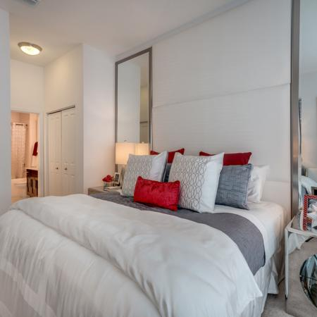 Image of furnished apartment bedroom with silver night stands and view of the bathroom