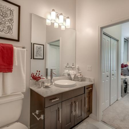 Image of apartment bathroom with marble vanity counter top and view of the bedroom