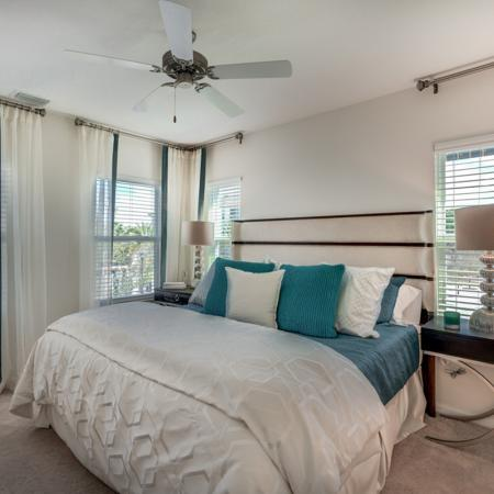 Image of furnished apartment bedroom with teal accents on the bed and an accent chair on the left