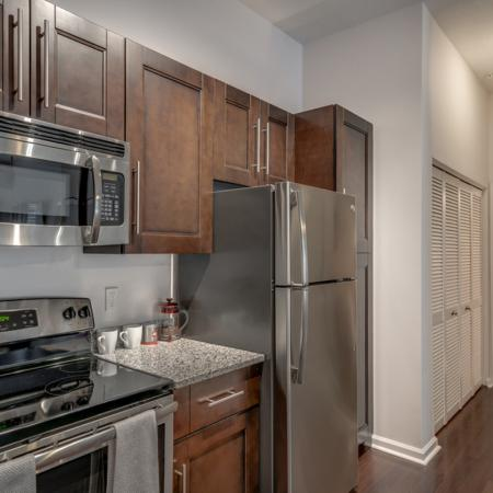 Image of apartment kitchen with custom cabinetry, stainless steel microwave, stove, fridge and entrance towards the bathroom