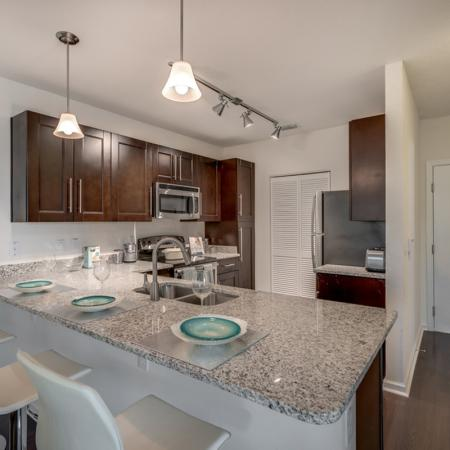 Image of apartment kitchen with granite counter top, stainless steel appliances and white bar stools