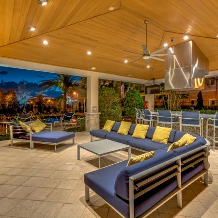 Image of resort-style cabana with blue outdoor furniture, flat screen tv, and entertainment area