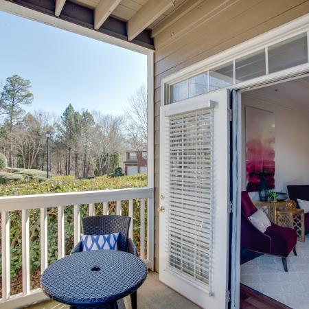 Image of apartment patio with outdoor furniture and view of apartment living room with accent chairs at Retreat at Peachtree City