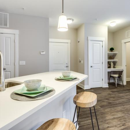 View of Renovated Apartment Interiors, Showing Living Room With Barstools, Built-In Shelving, and Laundry Room at Cottonwood Reserve Apartments